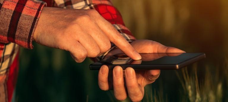 An Alabama farmer operates a mobile device