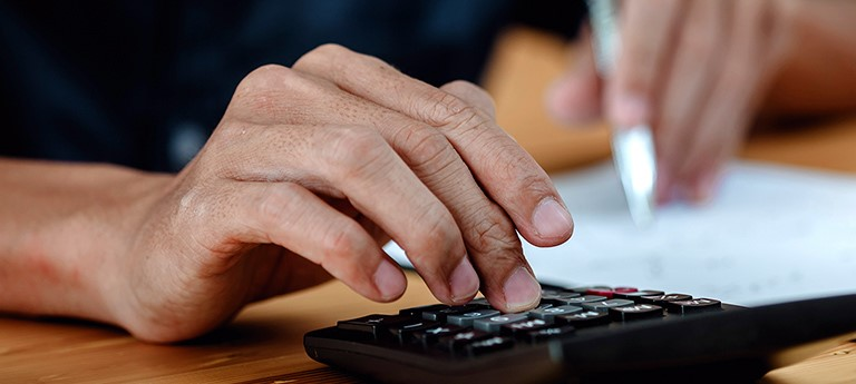 Close up of hands operating a calculator and writing notes
